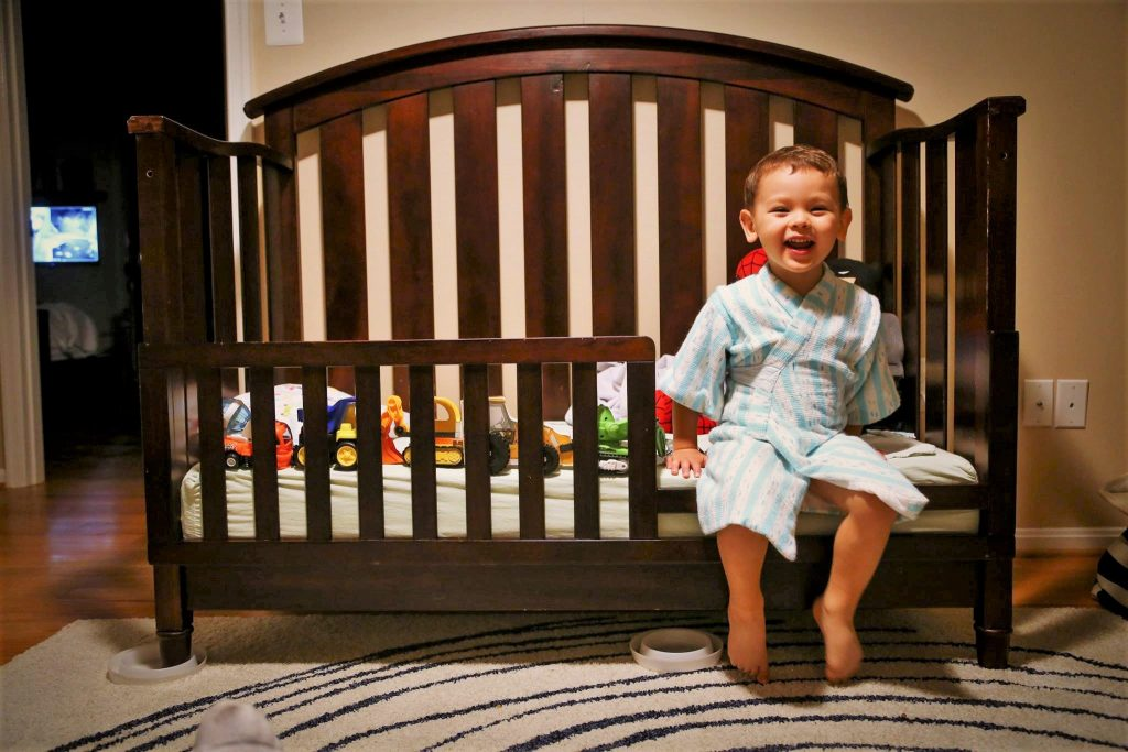 Toddler sitting on the edge of a toddler bed