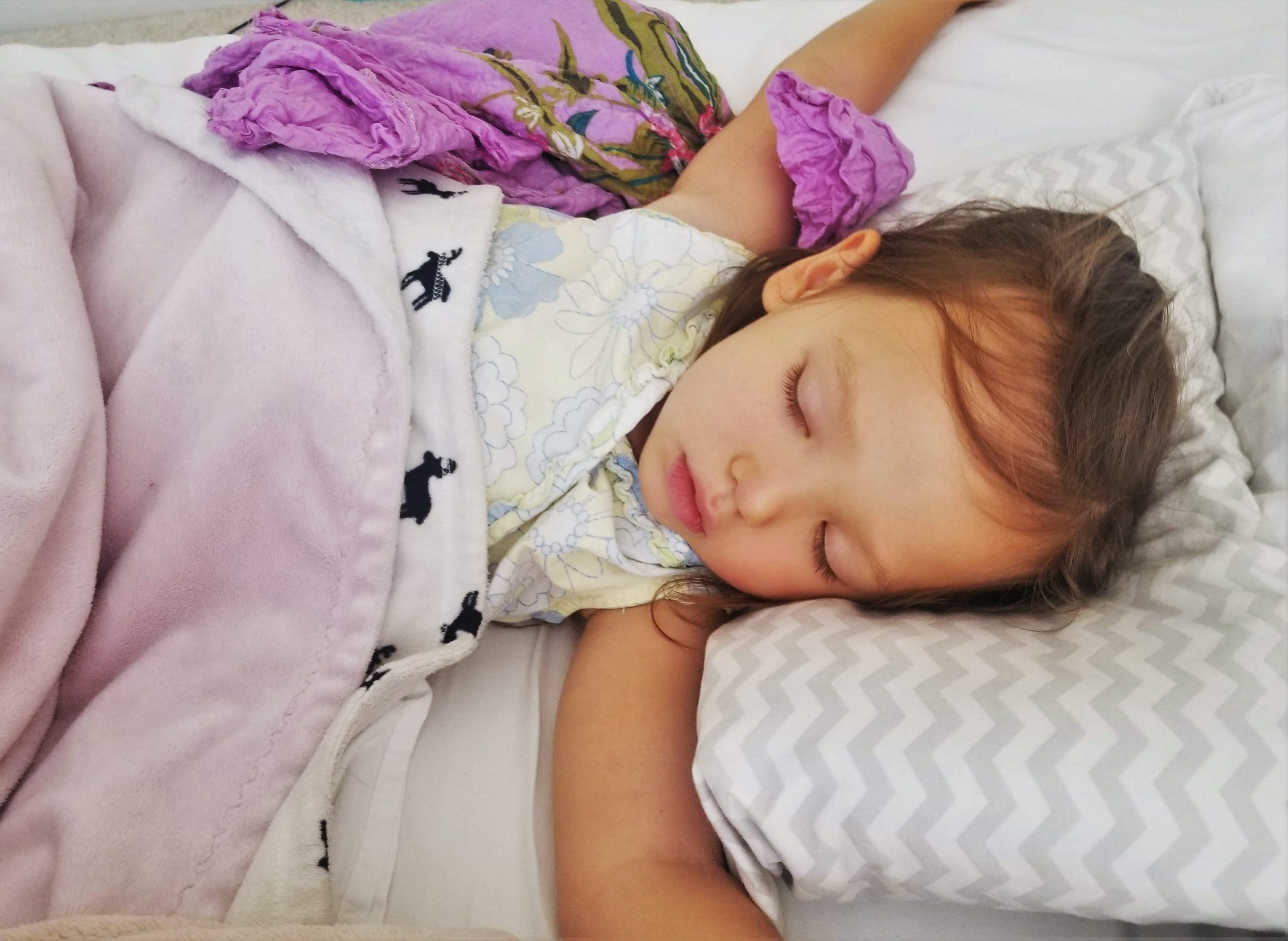Toddler girl sleeping with a blanket