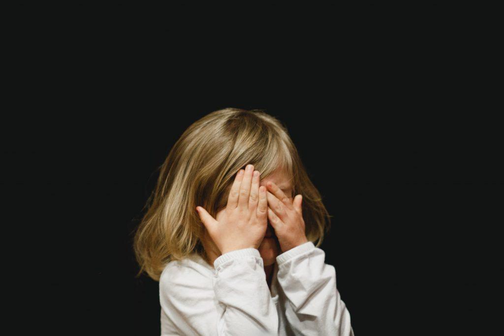 Toddler covering her eyes