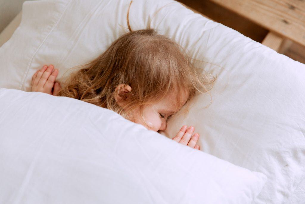 Toddler sleeping on white pillow