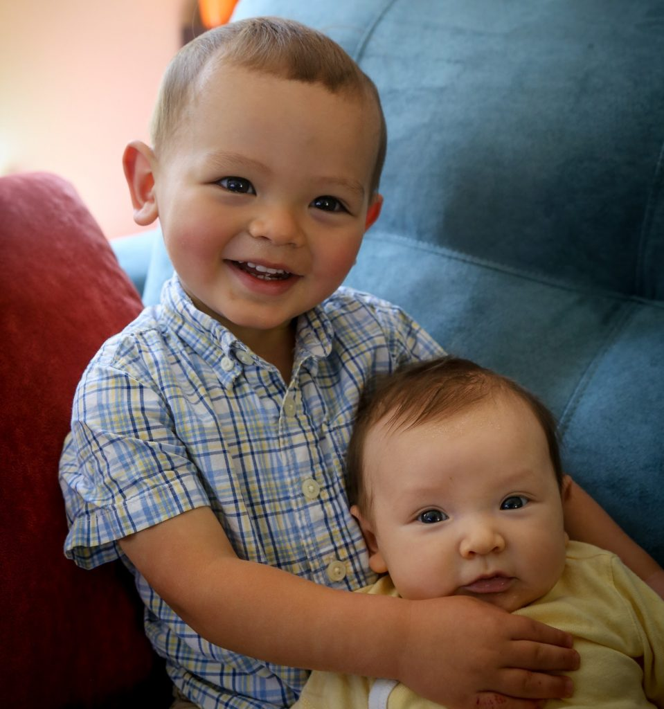 Toddler in button up shirt holding baby sister