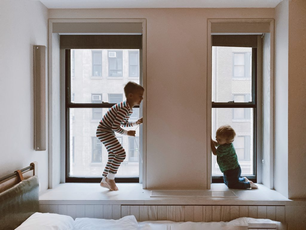 Older brother and younger brother playing in windows